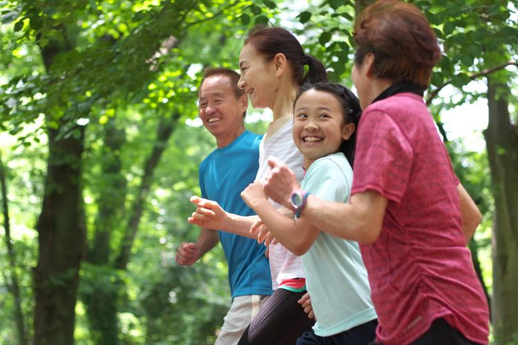Happy family jogging in the wood. Specially a young girl smiling against her elder relative.