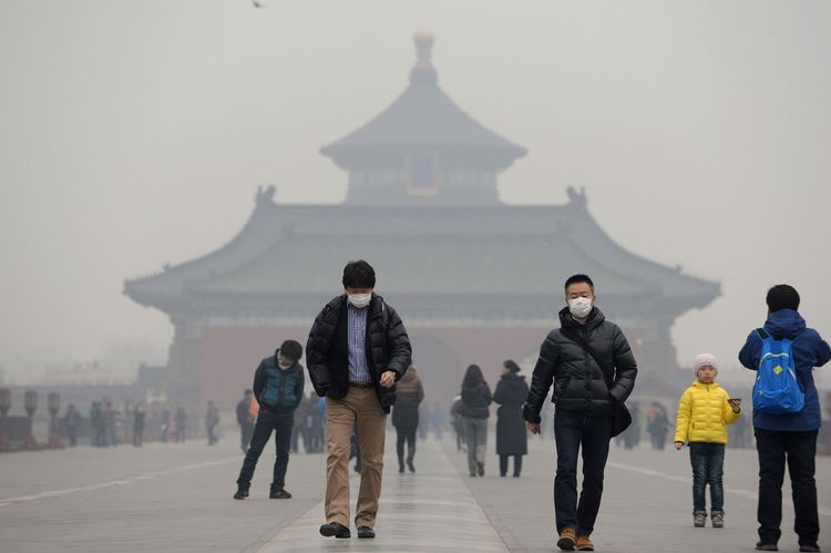 """This picture taken on February 24, 2014 shows visitors wearing masks in Temple of Heaven in haze-covered Beijing. Dangerous smog which has blighted swathes of northern China in recent days has prompted a spike in air purifier sales, local media reported Monday, as pollution continued to shroud Beijing. China's National Meteorological Centre issued a """"yellow"""" smog alert for much of the country's north on Monday, the fifth consecutive day of heavy pollution which has slashed visibility and seen pollution reach hazardous levels. CHINA OUT AFP PHOTO (Photo credit should read STR/AFP/Getty Images)"""